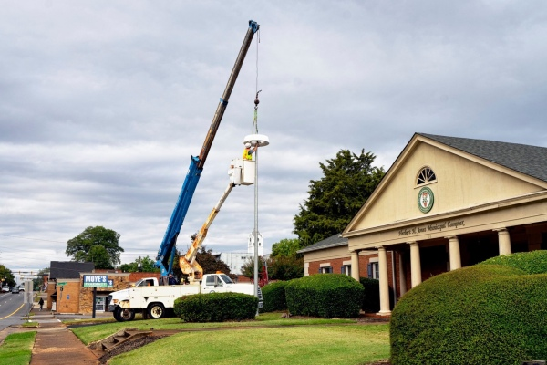 Photo of McDonough staff installing a solar powered light outside McDonough Fire Station 51 (city photo)