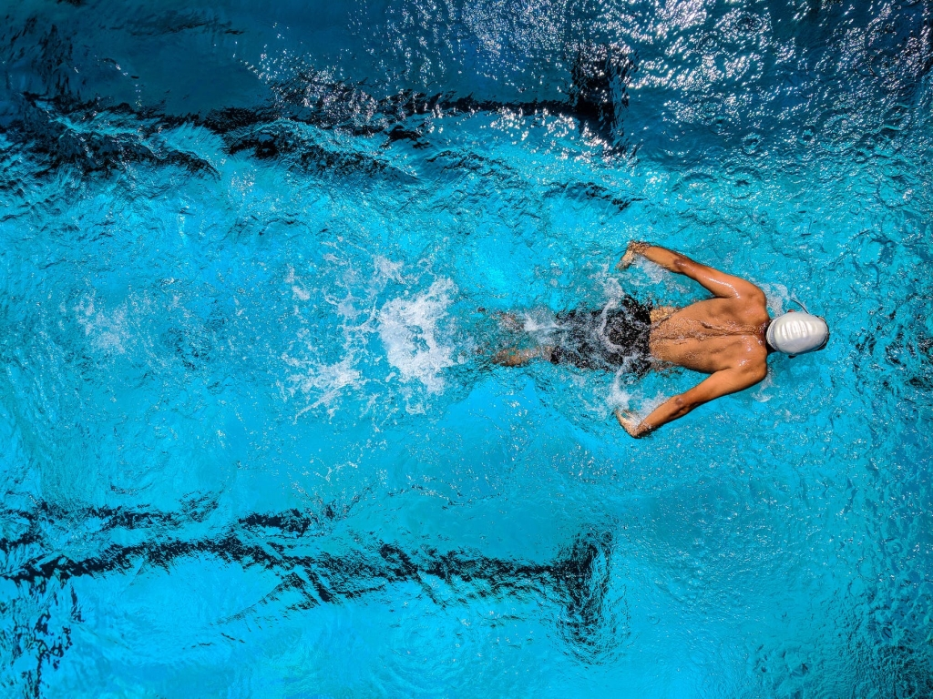 Photo of a competitive swimmer in a pool lane (Pexels photo)