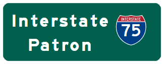 Green Road Sign with blue and red I-75 sign and white text Interstate Patron